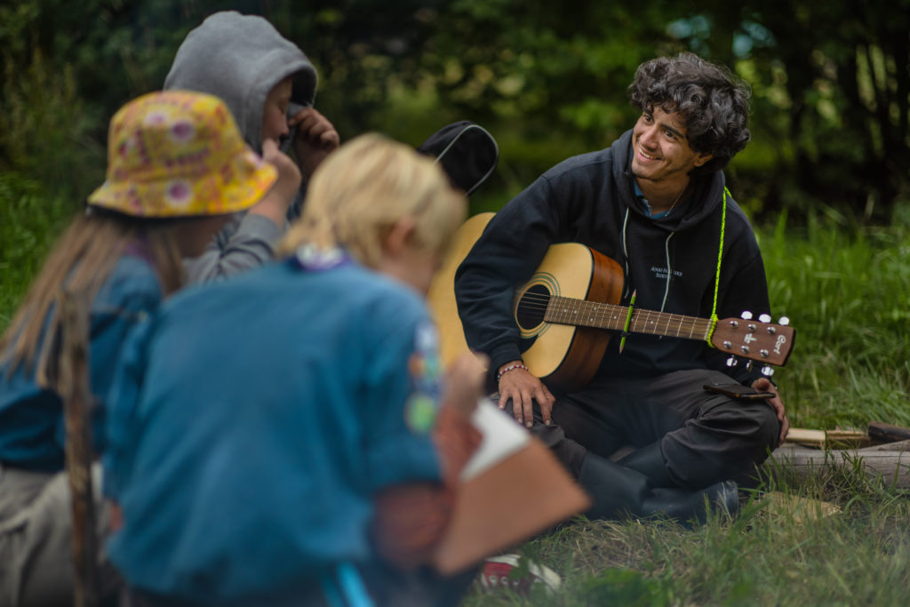 Scouter på läger: Tre scouter med ryggen mot kameran lyssnar på en scoutledare som spelar gitarr.